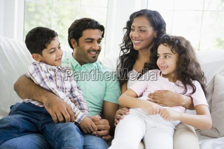 familie im wohnzimmer sitzt auf sofa