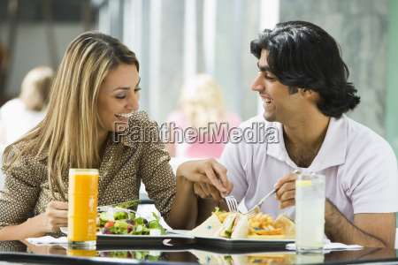 couple at restaurant eating and smiling