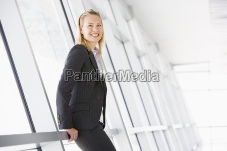 geschaeftsfrau stehen im korridor laechelnd