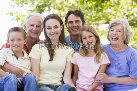 erweiterte familie im freien laechelnd