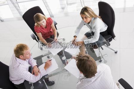 vier wirtschaftler in einem sitzungssaal mit