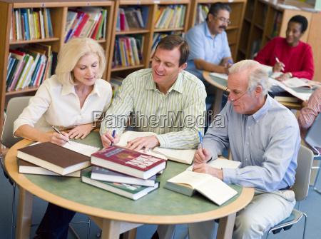 drei menschen in der bibliothek mit