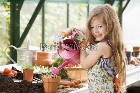 junges maedchen im gewaechshaus bewaesserung topfpflanze