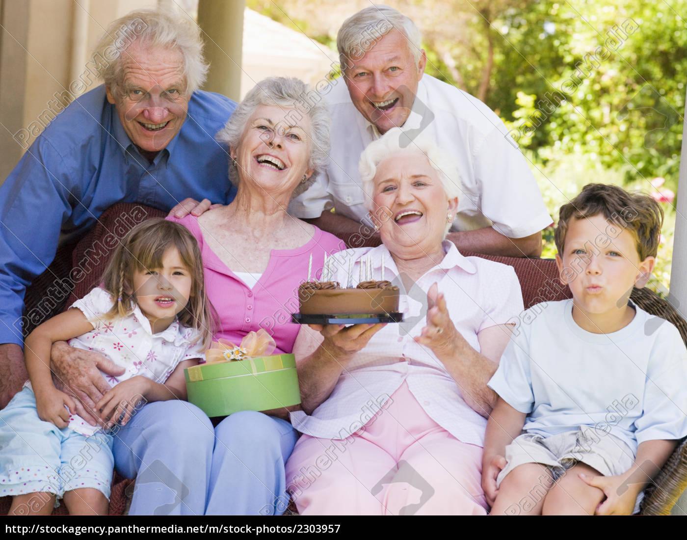 großeltern und enkel auf patio mit kuchen und geschenk ...