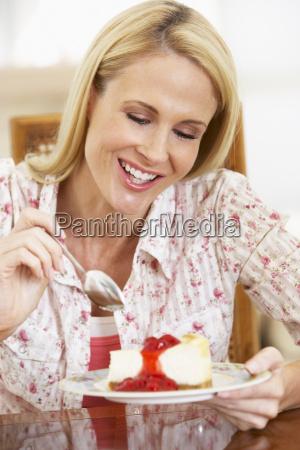 mittlere erwachsene frau die kaesekuchen isst