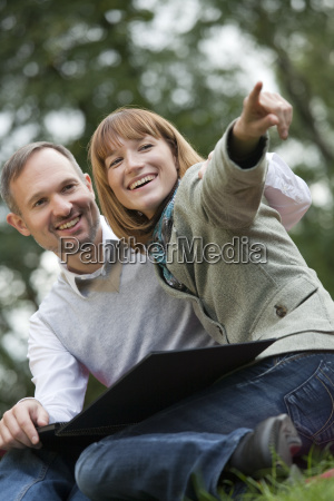 happy couple in park with photo
