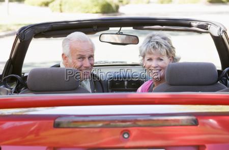 paare im umwandelbaren autolaecheln