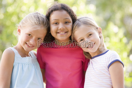 three young girl friends standing outdoors