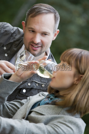 couple drinking by picnic