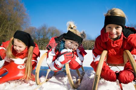 schwestern rodeln im schnee