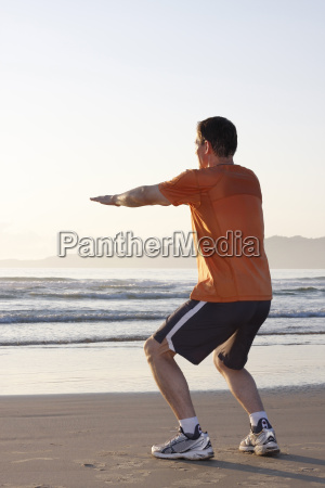 laeufer macht kniebeugen am strand