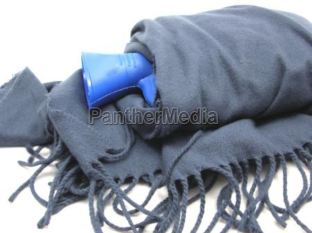 blaue waermflasche eingewickelt in blauen schal