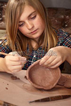 junges maedchen im lehmstudio machen schuessel