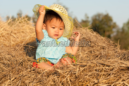 baby von asien sitzt auf stroh