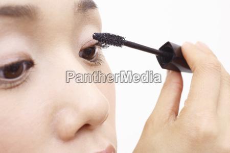 japanese woman applying mascara to eyelashes