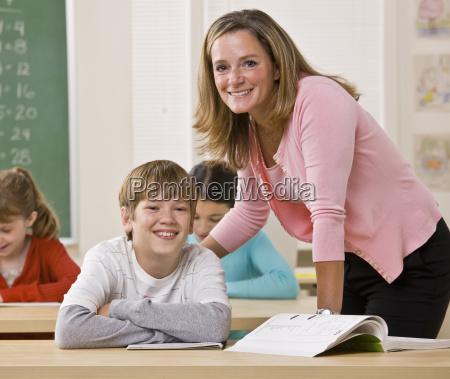 lehrer helfen schueler im klassenzimmer