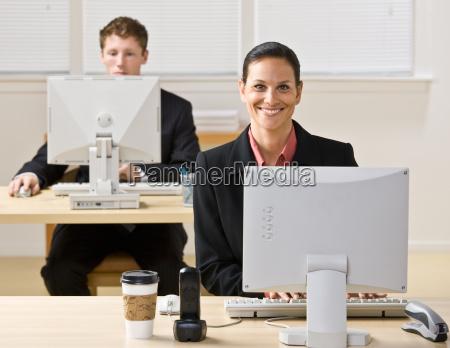 geschaeftsleute die auf computer eingeben
