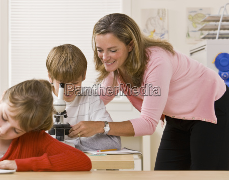 teacher helping student with microscope