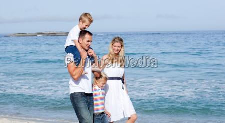lebhafte familie die auf den sand