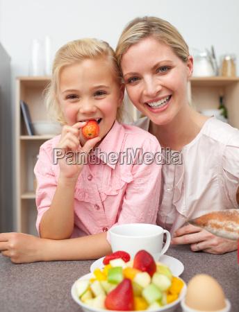 aufmerksame mutter die frucht isst mit