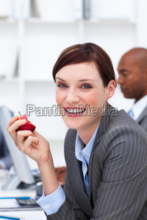 portrait of a smiling businesswoman eating
