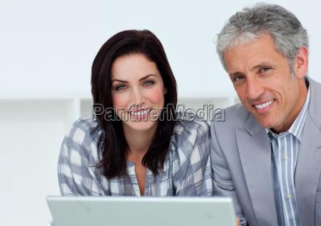 froehliche geschaeftsleute die am computer arbeiten