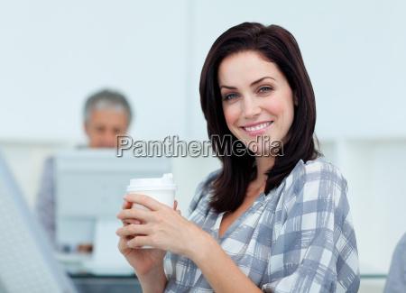 gluehende geschaeftsfrau trinkt einen kaffee