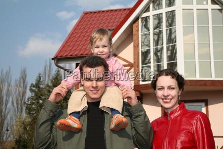 familie mit baby und haus