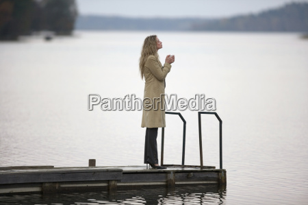 businesswoman standing on jetty holding cup