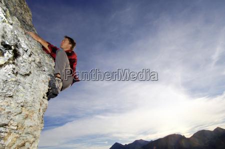 man rock climbing in mountains side