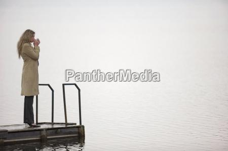 businesswoman standing on jetty drinking side