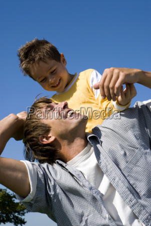 boy sitting on fathers shoulders