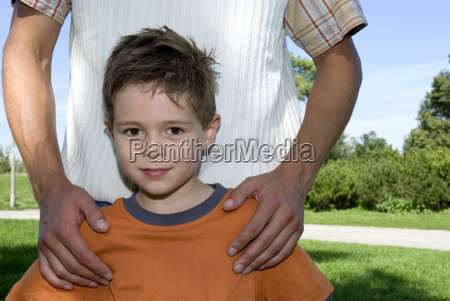 father standing behind son portrait