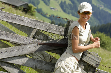 young woman leaning on wooden railings
