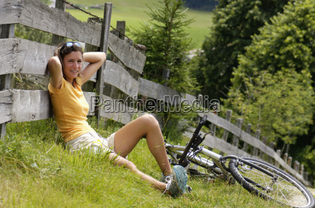 young woman sitting in meadow leaning