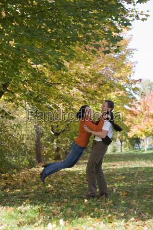 man lifting woman side view