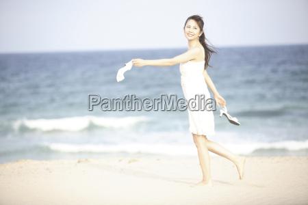 japanese woman walking along a beach