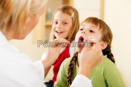 AErztin untersucht hals eines kindes