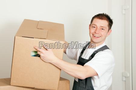 moebelpacker beim umzug hebt umzugskarton