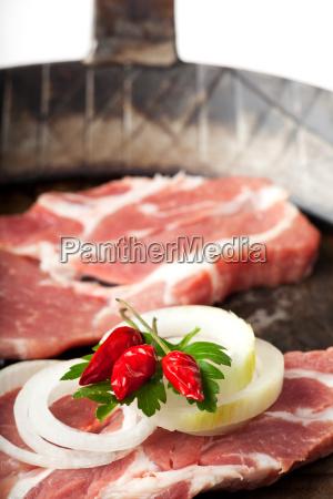 raw pork steaks in an iron