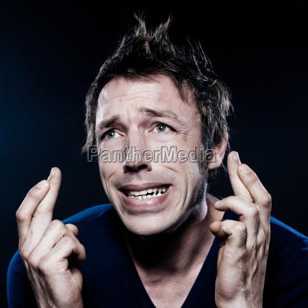 lustiges mann portraet mit gekreuzten fingern