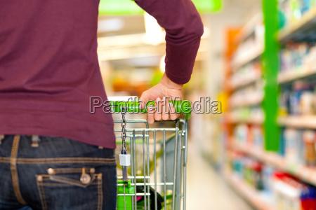 frau im supermarkt mit einkaufswagen
