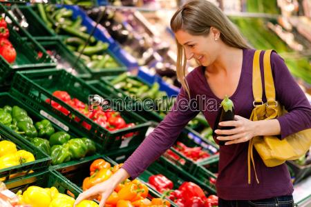 woman in supermarket buying groceries