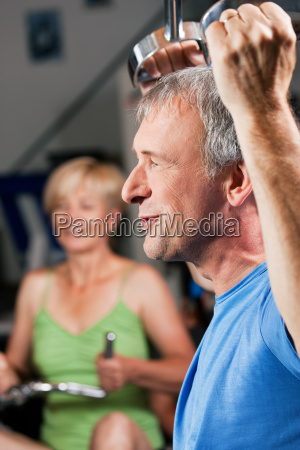 elderly couple exercising in the gym
