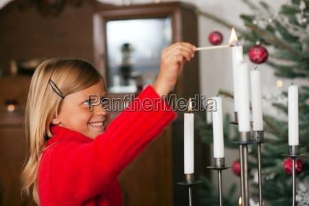 kind entzuendet weihnachtskerzen