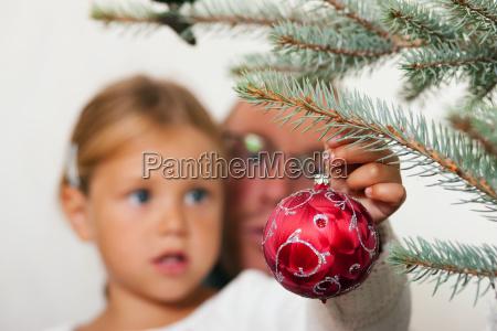 family decorates christmas tree