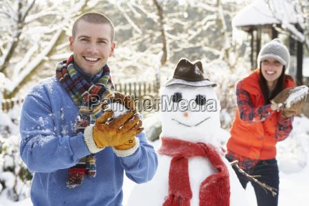 junges paar schneeball kampf im garten
