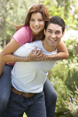 young man giving woman piggyback outdoors