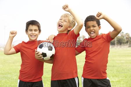 young boys im fussball team feiert