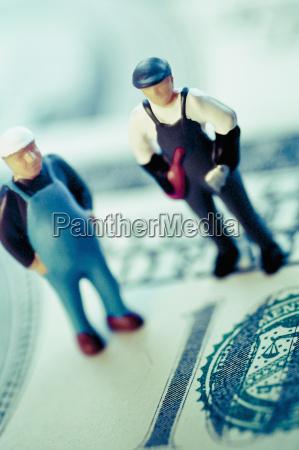figuren zweier bauarbeiter zur us papierwaehrung